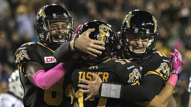 Tiger-Cats receiver Tasker celebrates his touchdown with quarterback Mathews and receiver Grant against the Roughriders during their CFL football game in Hamilton