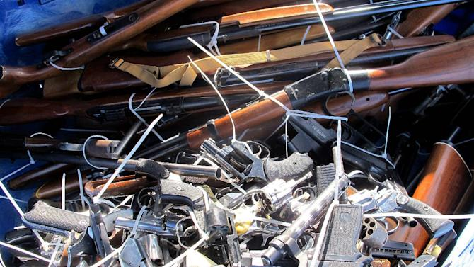 Guns are piled inside a crate outside a police station in Tucson, Ariz. on Tuesday, Jan 8, 2013, during Tucson City Councilman Steve Kozachik's gun buy back program. Kozachik asked people to turn in their guns for a $50 gift certificate to a grocery store. Tuesday marked the second anniversary of when  a gunman opened fire on former Rep. Gabrielle Giffords as she met with constituents in 2011, killing six people and leaving 12 others injured. (AP Photo/Brian Skoloff)