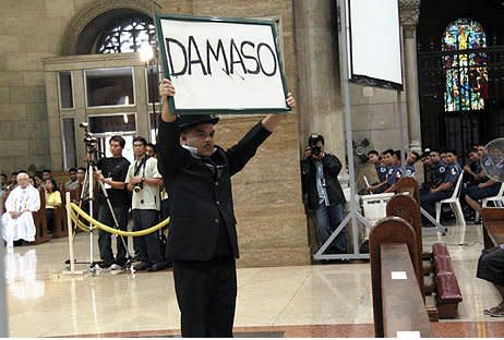 Carlos Celdran raises a placard that says 'Damaso' while wearing a topcoat and hat at the Manila Cathedral in Septemnber 2010. (Photo from Carlos Celdran's Facebook page)