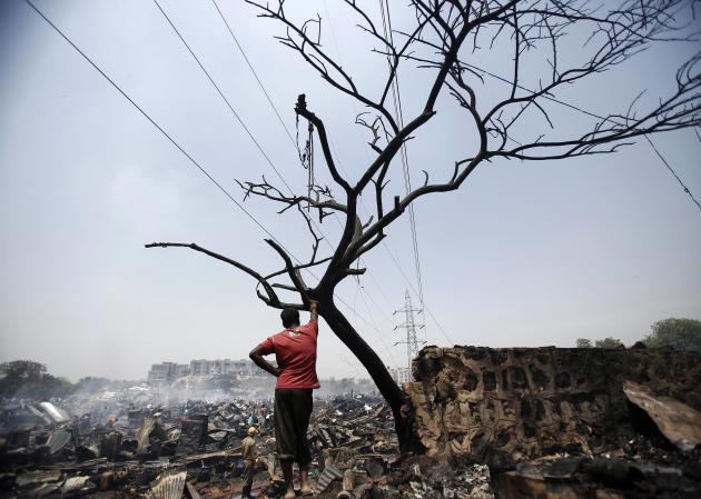 Resident stands next to the debris of huts after a fire broke out in a slum area in New Delhi