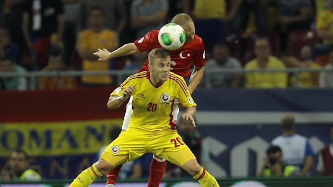 Turkey's Semih Kaya, rear, jumps for a header with Romania's Dragos Grigore during a World Cup Group D qualifying soccer match between Romania and Turkey at the National Arena stadium in Bucharest, Romania, Tuesday, Sept. 10, 2013