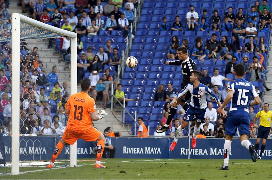 Real Madrid's Cristiano Ronaldo scores his third goal against Espanyol's Victor Alvarez and goalkeeper Kike Casilla during their Spanish first division soccer match at Power8 stadium in Cornel