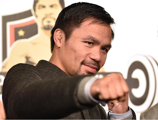 WBO welterweight world champion Manny Pacquiao poses for the media following a press conference at his boxing gym in Tokyo on November 25, 2016