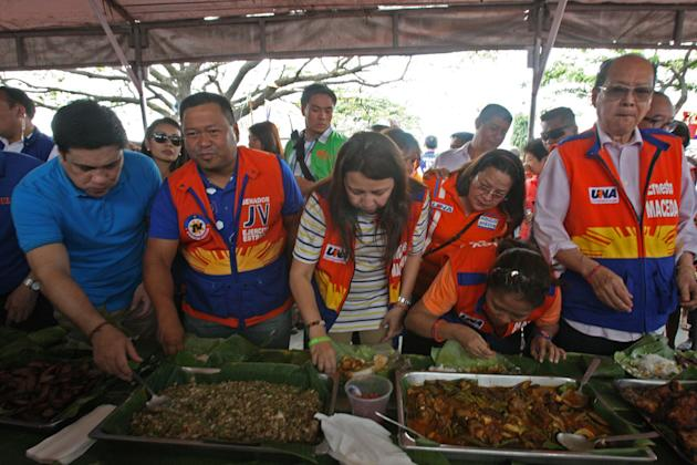 ALMU-CHOW SA PALENGKE. Senatorial candidates of the United Nationalist Alliance (UNA) share breakfast with market vendors in a 'boodle fight' buffet prepared by local leaders at the Angeles City Public Market during the coalition's Central Luzon campaign leg in Pampanga Wednesday (Feb. 20, 2013). Joining the UNA contingent in Pampanga are UNA bets Nancy Binay, Tingting Cojuangco, JV Ejercito Estrada, Dick Gordon, Ernesto Maceda, Mitos Magsaysay and Migz Zubiri. (Photo from UNA)
