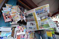 A Malaysian man reads a newspaper outside a shop in downtown Kuala Lumpur on October 10, 2012. — AFP pic