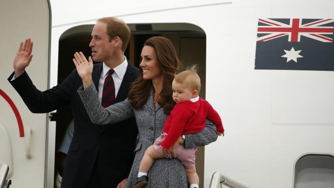 Britain's Catherine, the Duchess of Cambridge, waves with her husband Prince William, as she holds her son Prince George before they depart Canberra