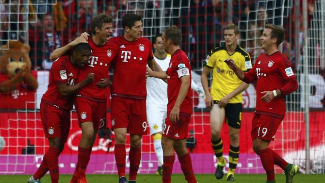 Bayern Munich's Mueller celebrates with team mates after scoring a goal against Borussia Dortmund during their German first division Bundesliga soccer match in Munich