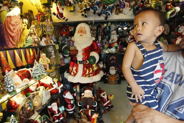 A child looks at a Christmas decor for sale inside a store in Manila November 19, 2012. The Philippines, a mainly Roman Catholic country in Southeast Asia celebrates one of the longest Christmas holiday in the world, playing Christmas carols in shopping malls in September and putting up lantern and fireworks early in December. REUTERS/Romeo Ranoco (PHILIPPINES - Tags: RELIGION SOCIETY)