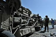 French soldiers with the NATO-led International Security Assistance Force (ISAF) look at the scene where a civilian minibus was hit by a remote-controlled bomb in Paghman district of Kabul