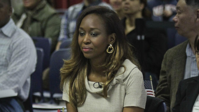 "Immaculee Ilibagiza clutches a small American flag as she listens during a naturalization ceremony at the U.S. Citizenship and Immigration Services (USCIS) on Wednesday, April 17, 2013 in New York. Ilibagiza, the author of the best-seller ""Left to Tell: Discovering God Amidst the Rwandan Holocaust"" became a naturalized American with 50 other immigrants at a Manhattan ceremony. She survived the 1994 Rwandan genocide that claimed more than a half-million lives. (AP Photo/Bebeto Matthews)"
