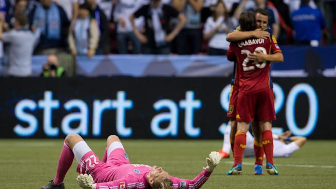 Vancouver Whitecaps goalkeeper David Ousted, left, of Denmark, lies on the field as Real Salt Lake's Luis Gil, right, and Ned Grabavoy celebrate a 1-0 win over the Whitecaps in an MLS soccer game Saturday, Sept. 28, 2013, in Vancouver, British Columbia