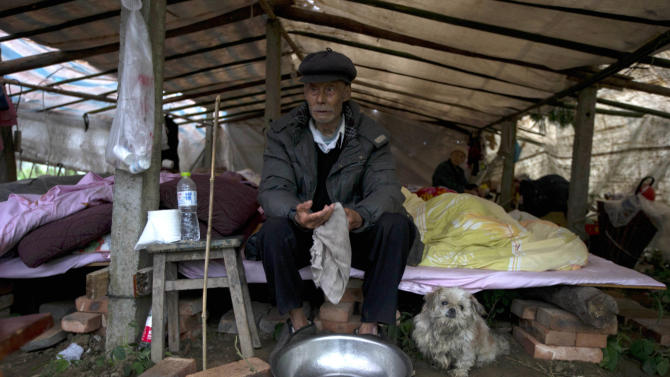 An elderly Chinese man waits for food to be distributed with his dog at a makeshift tent in Lushan county in southwestern China's Sichuan province, Monday, April 22, 2013. Saturday's earthquake in Sichuan province killed at least 186 people, injured more than 11,000 and left nearly two dozen missing, mostly in the rural communities around Ya'an city, along the same seismic fault where a devastating quake to the north killed more than 90,000 people in Sichuan and neighboring areas five years ago in one of China's worst natural disasters.  (AP Photo/Ng Han Guan)