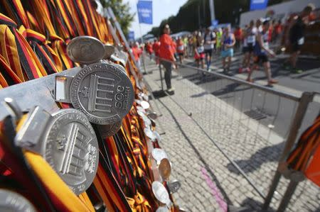 Runners walk past medals near the finish line at the Berlin marathon in Berlin