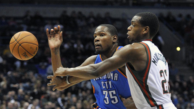 Oklahoma City Thunder's Kevin Durant (35) and Milwaukee Bucks' Khris Middleton scramble for a loose ball during the first half of an NBA basketball game Saturday, Nov. 16, 2013, in Milwaukee