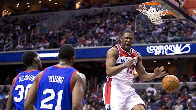 Philadelphia 76ers center Dewayne Dedmon, left, and forward Thaddeus Young, center, watch as Washington Wizards center Kevin Seraphin shouts after dunking the ball to score during the second half of an NBA basketball game on Monday, Jan. 20, 2014 in Washington. The Wizards defeated the 76ers 107-99