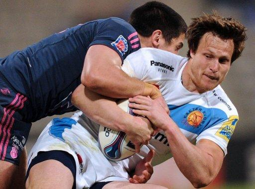 Centre Bryan Rennie (R) of Exeter Chiefs is tackled by Stade Français' centre Paul Williams