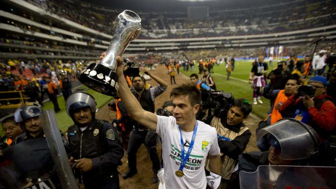 Leon player Ignacio Gonzalez  holds up the league trophy after beating America in the final match of the national soccer league championship in Mexico City, Sunday, Dec. 15, 2013