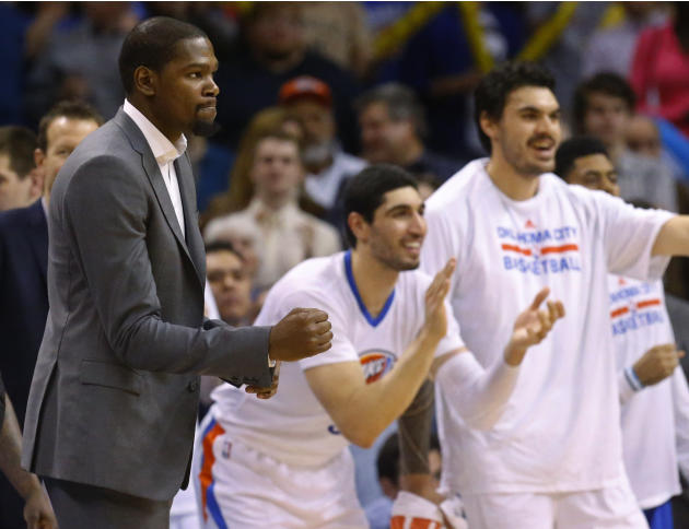 FILE - In this March 8, 2015, file photo, injured Oklahoma City Thunder forward Kevin Durant, left, pumps his fist as teammates Enes Kanter, center, and Steven Adams, right, cheer during the fourth qu
