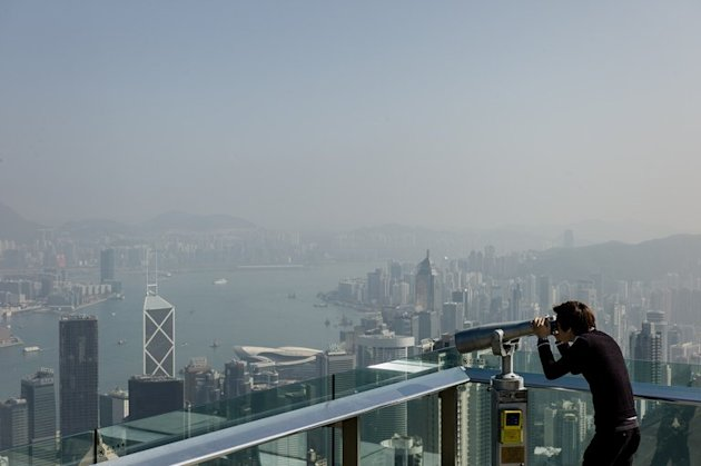 A tourist uses binoculars to view the city's skyline over a haze of pollution on a clear day in Hong Kong on February 1, 2013. A mainland Chinese mother who asked her son to relieve himself in a bottle in a crowded Hong Kong restaurant has sparked an outpouring of online anger in the latest bitter exchange over etiquette