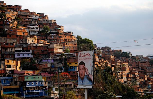 In this March 27, 2014 photo, a poster of Venezuela's late President Hugo Chavez stands in the Petare shanty town of Caracas, Venezuela. Many in Petare, a sprawling hillside slum of crumbling bric