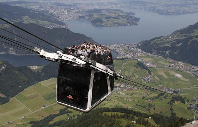 """People ride on the inauguration trip of the world's first open-air double-decker cable car system, the newly-built """"Cabrio"""", on the Stanserhorn Mountain, near Lucerne."""