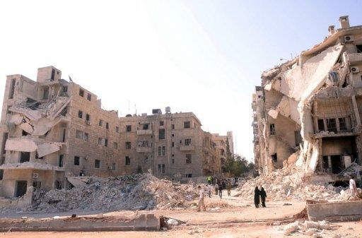 People walk past a row of destroyed buildings near the Al-Hayat Hospital in the northern Syrian city of Aleppo on September 10. Syrian troops on Tuesday pounded Aleppo to thwart a rebel advance in Syria's second city, activists said, as Hollywood star Angelina Jolie visited a Jordanian camp for refugees from the conflict