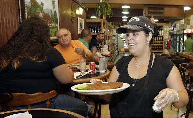 In this photo taken Friday, June 12, 2015, Judith Castro serves a lunch order at a local grocery store in the Little Havana area of Miami. The Institute for Supply Management, a trade group of purchas