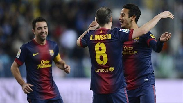 Barcelona midfielder Thiago Alcantara celebrates with Andres Iniesta after scoring against Malaga at la Rosaleda (AFP)