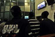 People watch a live broadcast of the trial of Liberian ex-leader Charles Taylor (on screen) inside the Special Court in Freetown April 26. Nations, rights groups and victims hailed a historic verdict after Taylor was convicted Thursday of aiding and abetting war crimes in Sierra Leone