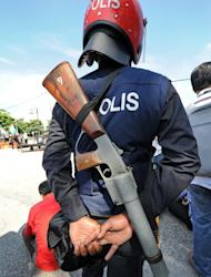 A Malaysia riot policeman stands guard with a smoke grenade rifle on his back outside an election nomination centre in Pekan on April 20, 2013. A total of 387 incidents were reported in the first three days of the two-week campaign, which kicked off Saturday, and at least 15 people have been arrested over the violence, national police spokesman Ramli Yoosuf told The Star newspaper