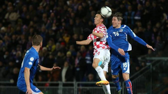 Croatia's Ivan Perisic jumps for the ball with Iceland's Olafur Ingi Skulason, right, during their World Cup qualifying playoff first leg soccer match in Reykjavik, Iceland, Friday Nov. 15, 2013