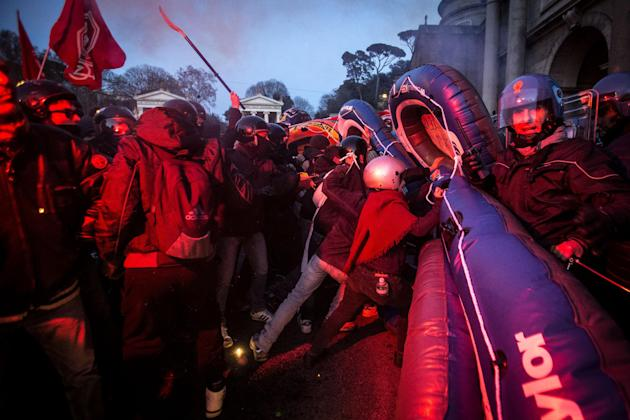Police officers clash with anti-Northern-League activists in Rome's central Piazza del Popolo square, Friday, Feb. 27, 2015. Police cleared out the square on the eve of a rally by Italy's righ