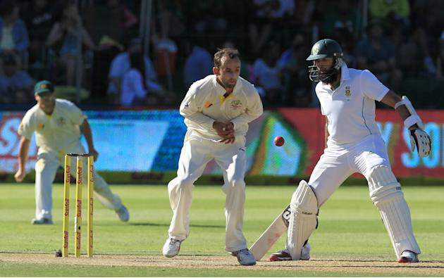 Australia's bowler Nathan Lyon, center, misfields his own bowling as South Africa's batsman Hashim Amla, right, reacts on the third day of their 2nd cricket test match at St George's Park