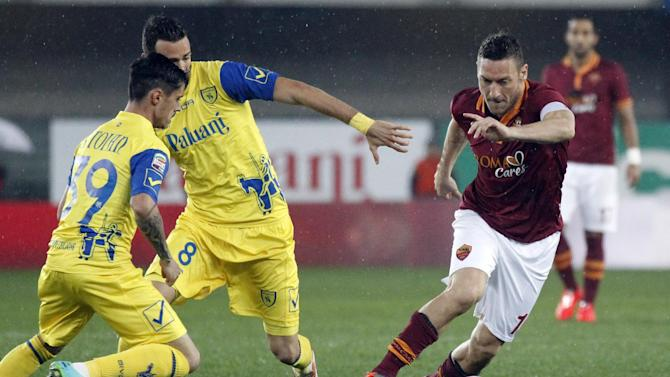 AS Roma's Francesco Totti, right, is chased by Chievo's Adrian Stoian, left, of Romania, and teammate Ivan Radovanovic, of Serbia, during a Serie A soccer match at Bentegodi stadium in Verona, Italy, Saturday, March 22, 2014