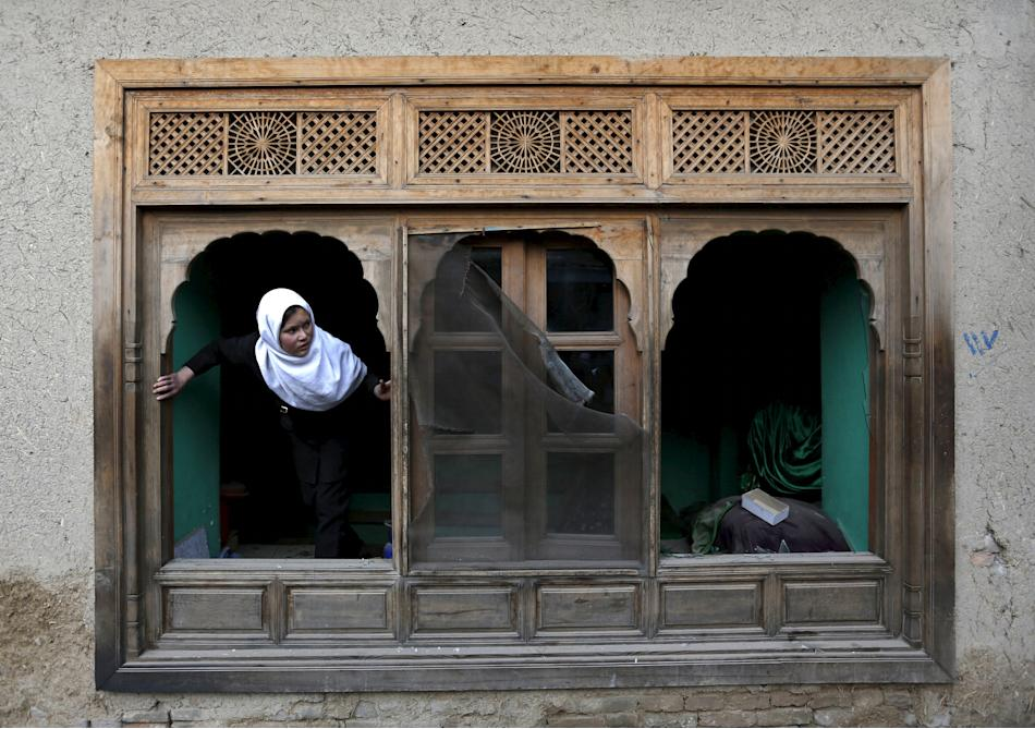 Afghan girl looks out of a damaged window of a shrine after a suicide attack in Kabul