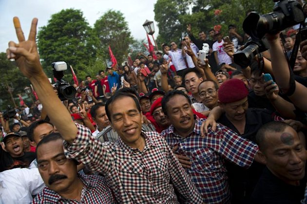 Indonesian frontrunner presidential candidate Joko Widodo, (C-L), popularly known by his nickname Jokowi, greets supporters during campaign for the July 9 election, in his hometown in Solo city, central Java island, on June 14, 2014