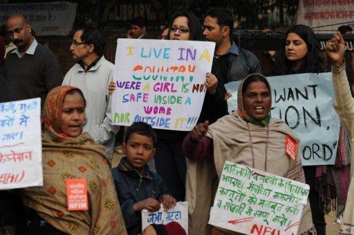 Indian protesters hold placards during a rally in New Delhi on December 31,2012 over the gang-rape of a young woman. The gang of men tried to run their victim over after the fatal attack, reports said, citing a grisly police account of the incident.