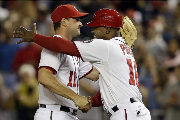 Washington Nationals third base coach Bo Porter (16) embraces third baseman Ryan Zimmerman (11) after their 4-1 win over the Los Angeles Dodgers, earning them a playoff spot, during their baseball gam