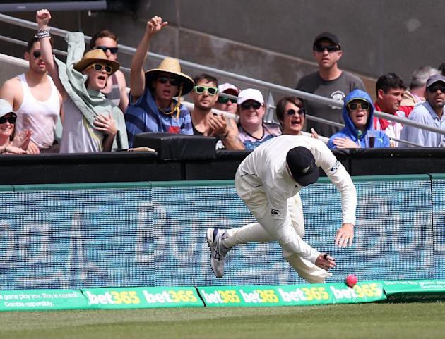 New Zealand's Martin Guptill is late getting to the boundary to stop 4 runs by Australia during their cricket test in Adelaide, Australia, Saturday, Nov. 28, 2015. This match is the sport's fi