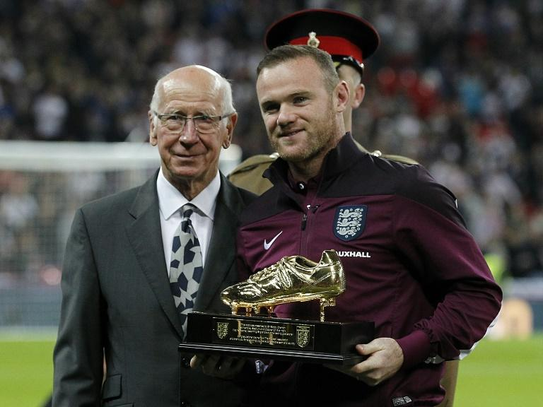 England and Manchester United footballer Wayne Rooney (R) poses for pictures with Sir Bobby Charlton after being presented with a gold plated commemorative boot before the Euro 2016 qualifying group E
