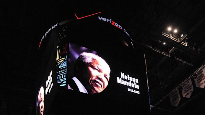 An image of  former South African President Nelson Mandela, who died Thursday, is displayed on the scoreboard before an NBA basketball game between the Washington Wizards and the Milwaukee Bucks, Friday, Dec. 6, 2013, in Washington