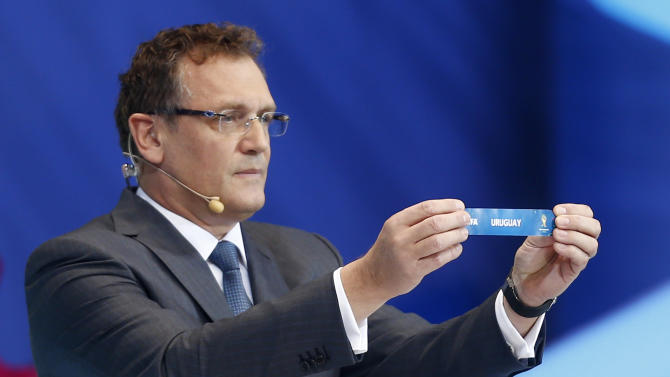 FIFA Secretary General Jerome Valcke holds the ticket of Uruguay during the draw ceremony for the 2014 soccer World Cup in Costa do Sauipe near Salvador, Brazil, Friday, Dec. 6, 2013