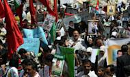 """Palestinians hold pictures of incarcerated relatives during a rally in the West Bank city of Nablus, May 8, in solidarity with prisoners on hunger strike. UN chief Ban Ki-moon urged Israel to try or release hunger-striking Palestinian prisoners after activists denounced his """"silence"""" in a protest outside the UN's West Bank offices"""