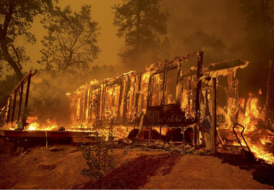 A home burns as the Butte Fire rages through Mountain Ranch