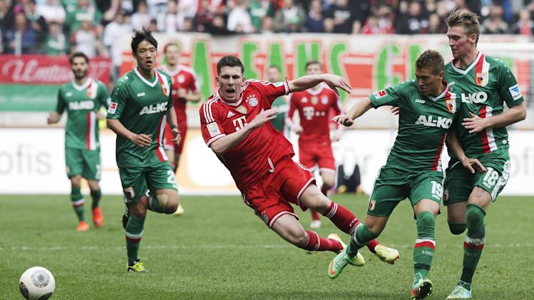 Bayern's Pierre Hojbjerg of Denmark, center, and Augsburg's Matthias Ostrzolek, second right, and team mate Jan-Ingwer Callsen-Bracker challenge for the ball during the German first division Bundesliga soccer match between FC Augsburg and FC Bayern Munich, in Augsburg, southern Germany, Saturday, April 5, 2014