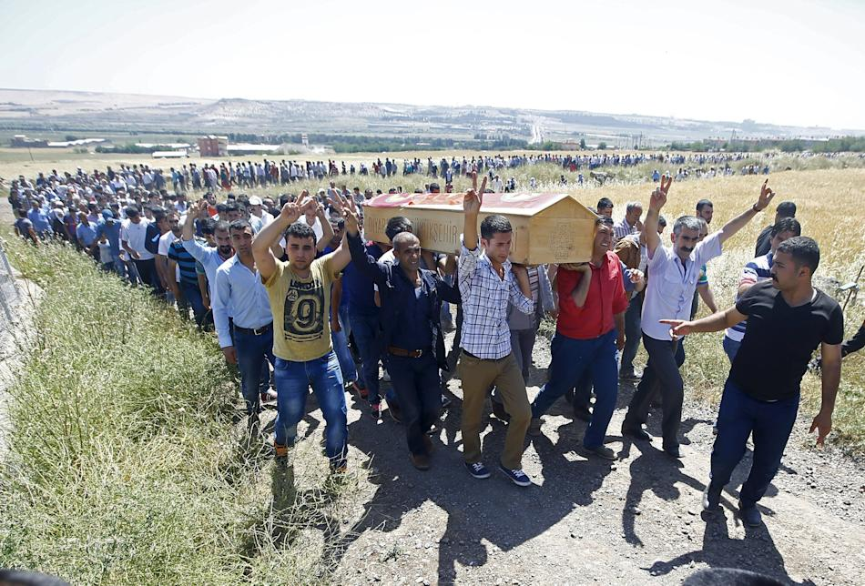 Kurdish mourners carry the coffin of Ramazan Yildiz, one of the victims in Friday's explosion, during his funeral at a cemetery in Diyarbakir