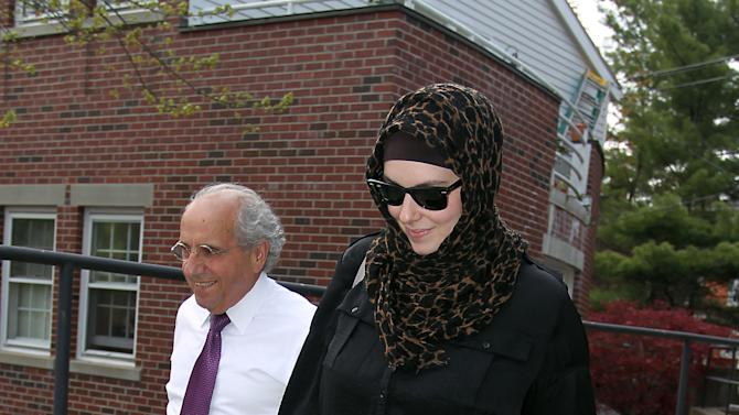 FILE - In this April 29, 2013 file photo, Katherine Russell, wife of Boston Marathon bomber suspect Tamerlan Tsarnaev, right, leaves the law office of DeLuca and Weizenbaum with Amato DeLuca, in Providence, R.I. Relatives of Tsarnaev, the older of the brothers suspected in the Boston Marathon bombing, will claim his body now that his wife has agreed to release it, an uncle said as officials in the U.S. and Russia deepened their investigations into him. (AP Photo/Stew Milne, File)