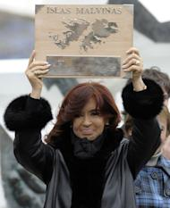 In this picture taken on April 2, 2012, Argentine President Cristina Kirchner holds a plaque claiming sovereignty over the Falkland Islands. Argentina and Britain fought a brief but bloody war over the islands in 1982, and diplomatic tensions have escalated in recent years with the discovery of oil near the Falklands
