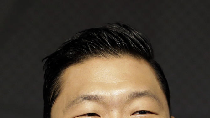 "FILE - In this Sept. 25, 2012 file photo, South Korean rapper PSY, who sings the popular ""Gangnam Style"" song, smiles during a press conference in Seoul, South Korea. As ""Gangnam Style"" gallops toward 1 billion views on YouTube, the first Asian pop artist to capture a massive global audience has gotten richer click by click. So too has his agent and his grandmother. But the money from music sales isn't flowing in from the rapper's homeland South Korea or elsewhere in Asia. With one song, 34-year-old Park Jae-sang — better known as PSY — is set to become a millionaire from YouTube ads and iTunes downloads, underlining a shift in how money is being made in the music business. (AP Photo/Lee Jin-man, File)"