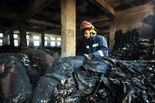 "A Bangladeshi fire-man examines burnt materials after a fire in the nine-storey Tazreen Fashion plant in Savar. Hong Kong sourcing giant Li & Fung said Sunday it was ""distressed"" by the deaths of 110 workers in a fire at a Bangladesh garment factory where it placed orders and offered compensation."